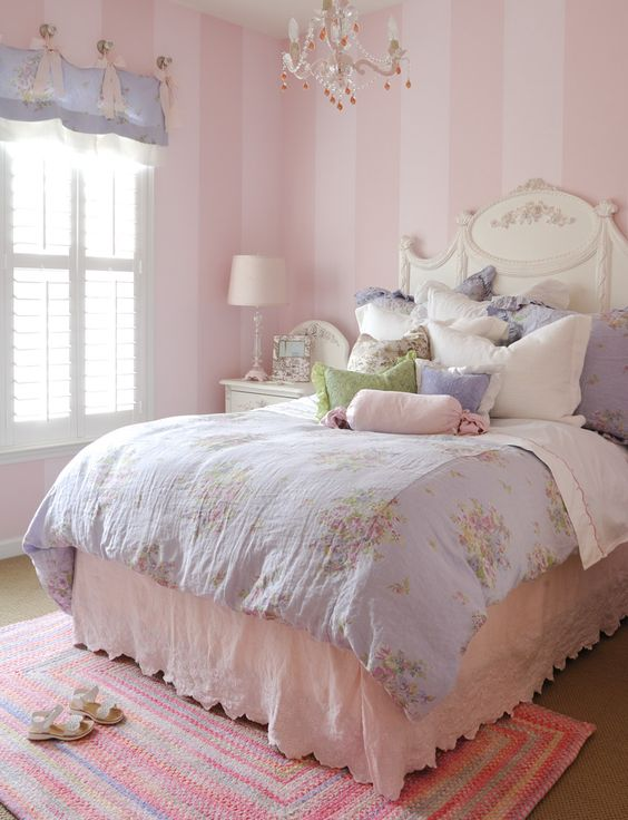 a vintge to shabby chic kid's bedroom with pink striped walls, a refined white bed, pastel floral bedding, a purple curtain and a crystal chandelier