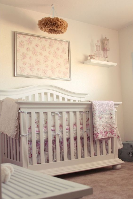 a shabby chic nursery with neutral walls and furniture, floral bedding and textiles and a paper fluff chandelier
