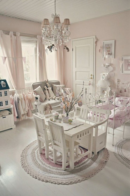 a pink and white vintage meets shabby kid's room with elegant white furniture, a crystal chandelier, pink bedding and curtains, a pretty gallery wall