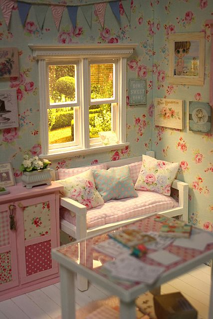 a pastel shabby chic kid's room with floral walls, pastel furniture, floral and plaid bedding, a colorful banner over the space