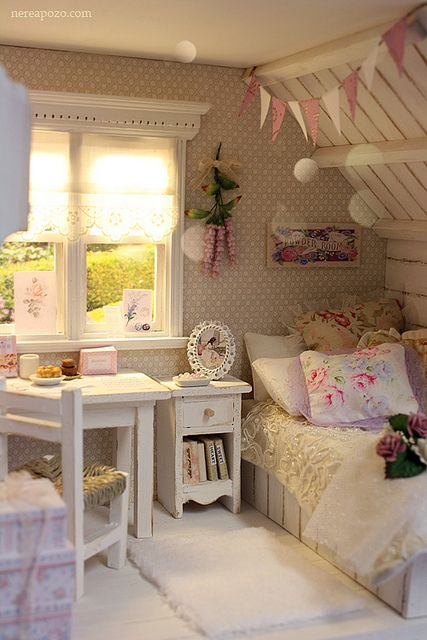 an attic shabby chic bedroom with printed wallpaper, rustic and vintage furniture in white, pastel and floral bedding and buntings over the bed