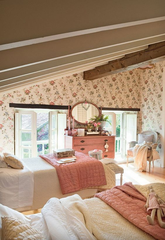 an attic shared kids' bedroom with floral wallpaper, wooden beams, vintage furniture, pink bedding and a dresser and a pink framed mirror