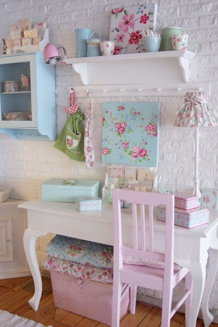 a shabby chic kid's room with white brick walls, beautiful white and pastel furniture, floral artworks and textiles and some other floral touches including lamps and artworks