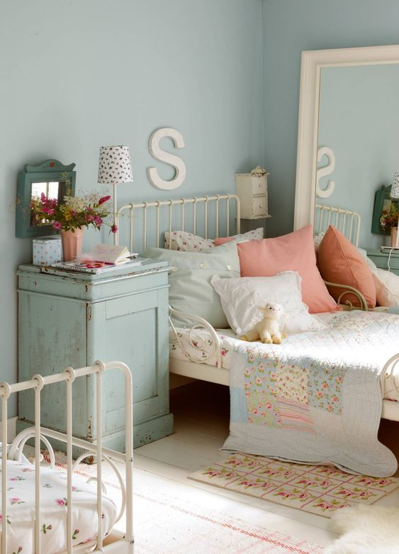 a shabby chic shared kids' bedroom with white metal beds, a large mirror, a blue nigthstand and pretty floral bedding