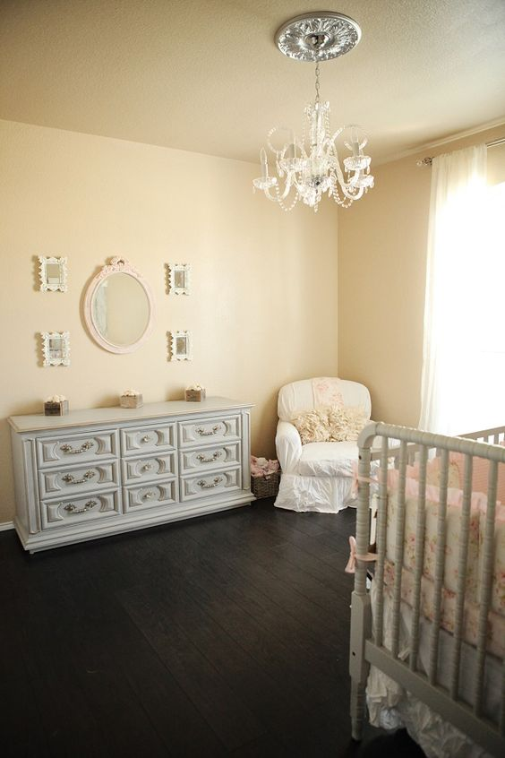 a shabby chic nursery with tan walls, elegant grey furniture, a white chair, a pretty vintage chandelier and a gallery wall with mirrors