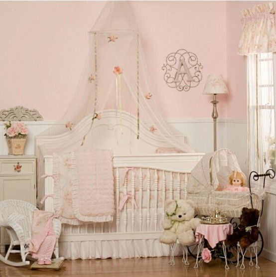 a pink and white shabby chic bedroom with pink walls and white paneling, neutral furniture, floral bedding and lamps and lots of toys
