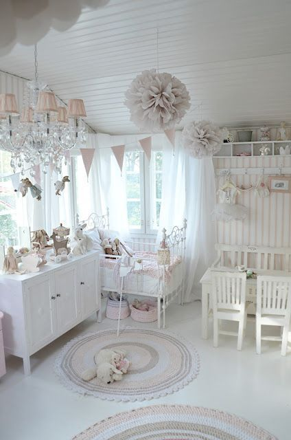 a blush and white shabby chic kid's room with pink and blush textiles, lamps and garlands, a crystal chandelier, and a metal bed
