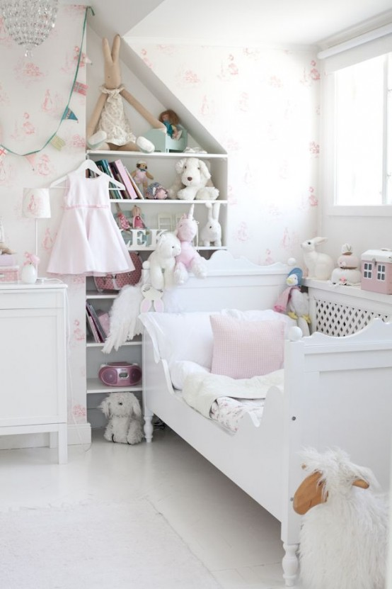 a white and blush shabby chic kid's room with floral wallpaper, chic white furniture, built-in shelves and lots of toys and a crystal chandelier over the space
