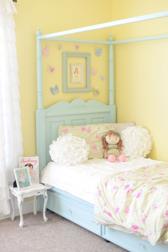 a pastel shabby chic bedroom with yellow walls, a blue bed, floral bedding, empty frames and butterflies is very chic and bright