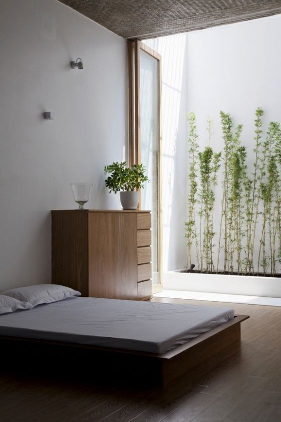 a minimalist zen bedroom with simple wooden furniture, white bedding, some lights connected to a small private garden outdoors