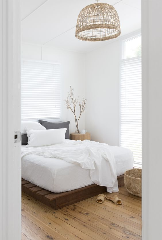 a neutral zen bedroom with a pallet bed, neutral bedding, a woven lamp, a basket and some branches in a vase