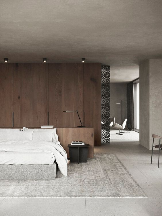 a modern zen bedroom with a wooden accent wall, an upholstered bed with white bedding, a black metal nightstand and lights
