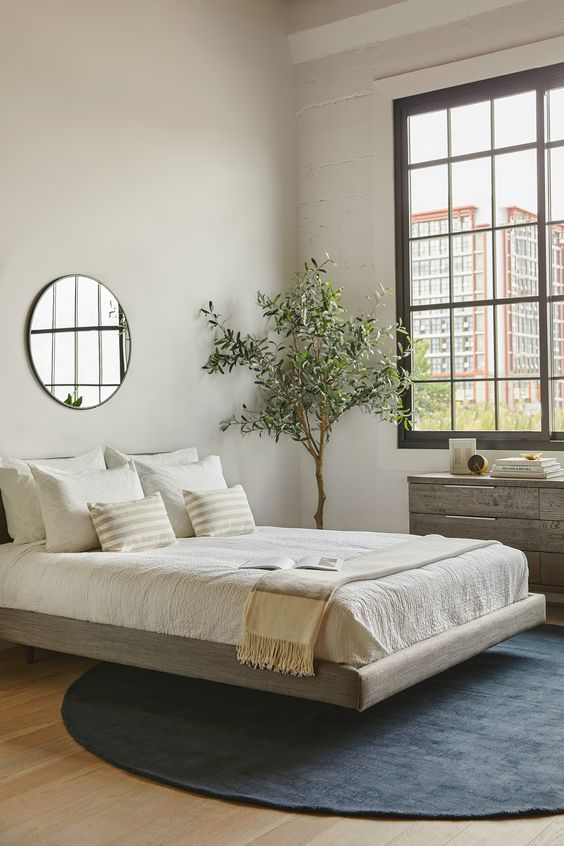 a modern zen bedroom with a grey floating bed, a reclaimed wooden dresser, a statement plant, neutral bedding and a round mirror