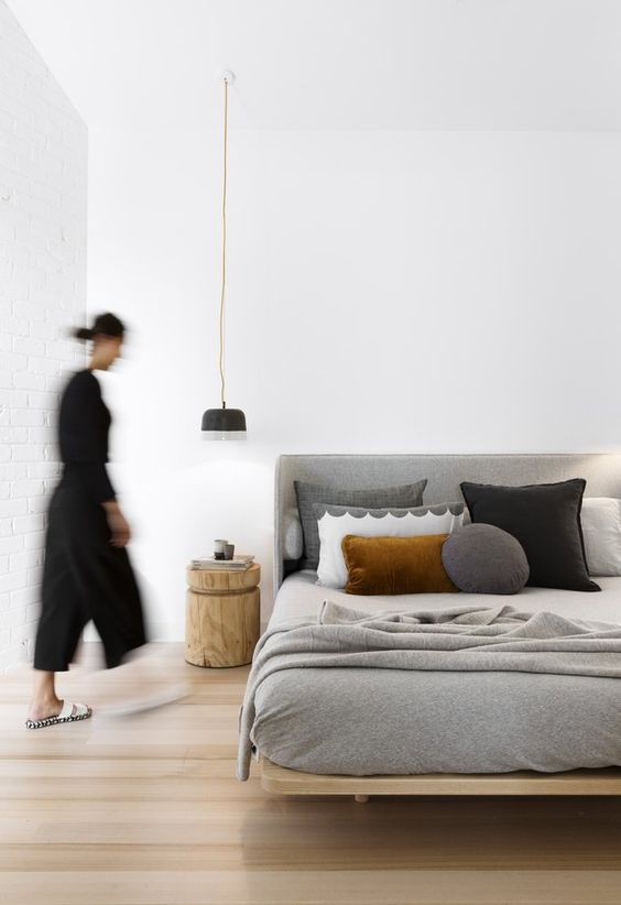 a stylish and neutral zen bedroom with a comfy wooden bed, grey and black bedding, a wooden nightstand and a pendant lamp