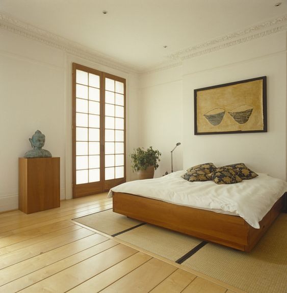 a relaxed zen bedroom with a wooden bed and a stand with a statue, a statement plant, neutral bedding and a bold artwork