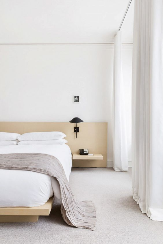 a neutral and welcoming zen bedroom with light-colored wooden bed and nightstands, black sconces and white textiles