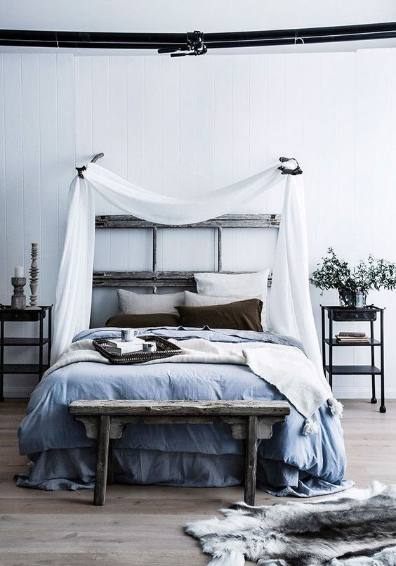 a relaxed zen bedroom with a reclaimed wooden bed, a bench, metal nightstands, blue and grey bedding and a canopy over the bed
