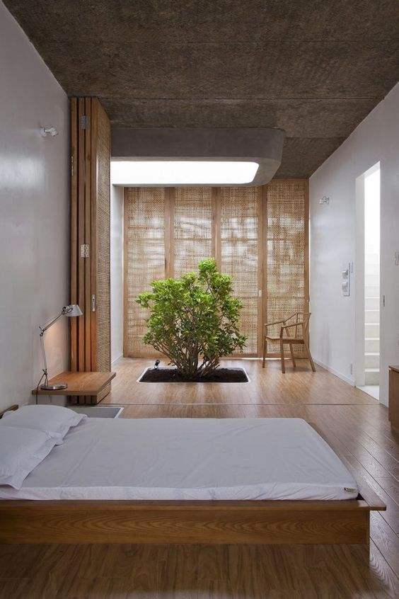 a natural zen bedroom with low wooden furniture, a planted tree, wooden screens and space dividers is a unique space