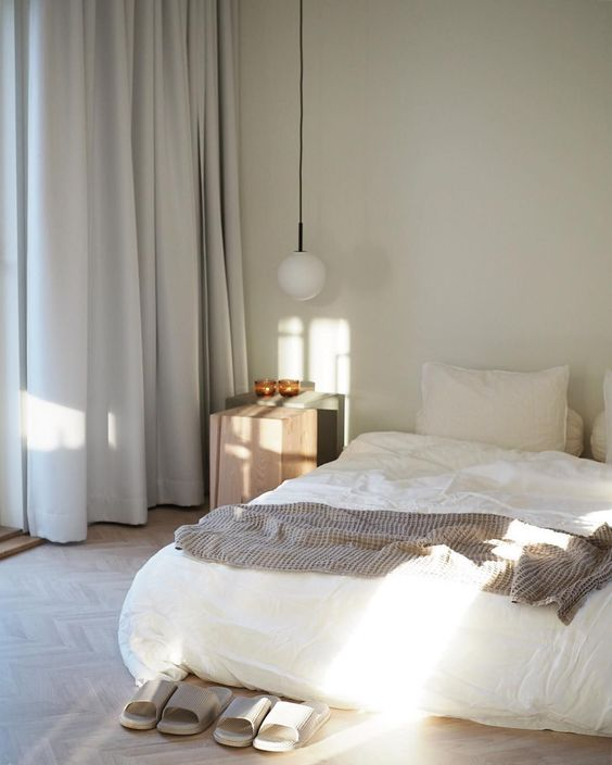 a zen-like bedroom with a bed right on the floor, a wooden nightstand, a pendant lamp and neutral bedding is chic