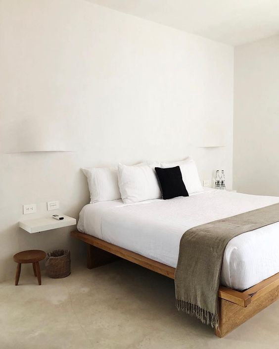 a very simple zen bedroom with a simple wooden bed, a low stool and floating nightstands, neutral bedding and wall lamps