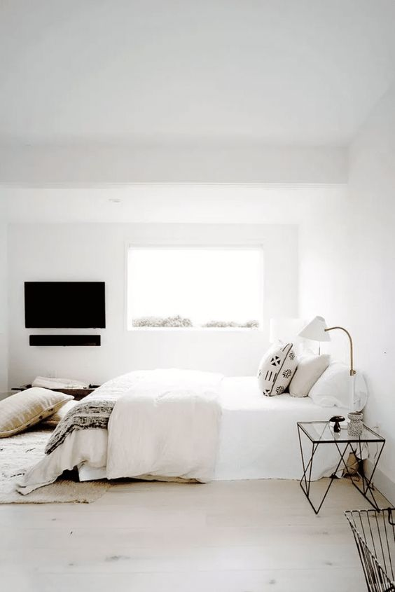 a welcoming zen bedroom with a bed, lightweight glass nightstands, sconces, pillows and blankets
