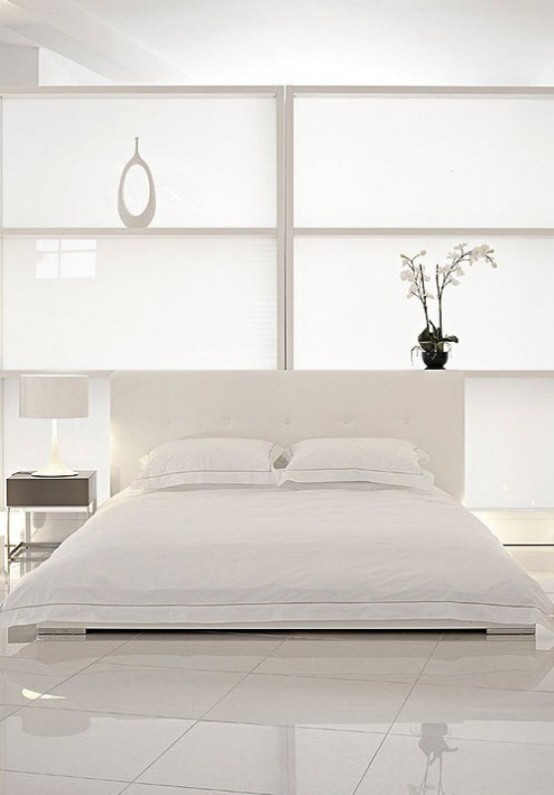 a minimalist white bedroom with a zen feel, with a polished white floor, white space divider, a nightstand and blooms and a pretty modern vase