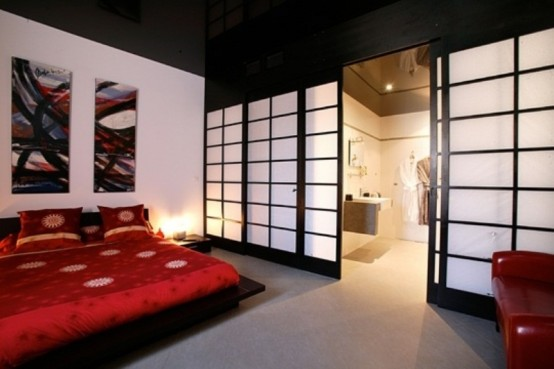 a bold Asian bedroom with a traditional zen feel, dark and red furniture, Asian sliding doors and bright bedding and a gallery wall in bright shades