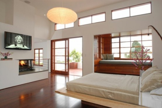 a neutral Japanese-style zen bedroom with a wooden bed, a daybed by the windowsill, a built-in fireplace and paper lamps