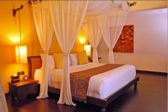 A Zen Bedroom With Low Dark Wooden Furniture, A Canopy Over The Bed, Some Table Lamps And A Bright Artwork