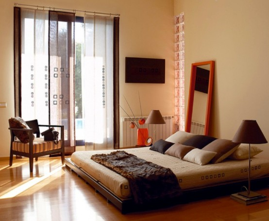 A Bold Asian Zen Bedroom With Tan Walls, A Dark Wooden Bed And A Chair, Catchy Curtains And A Red Frame Mirror