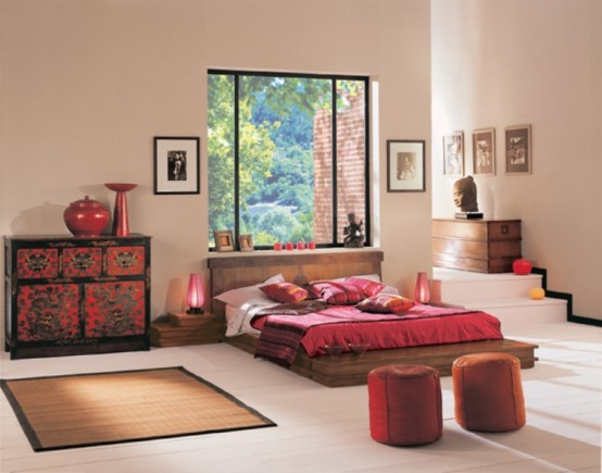 a colorful zen bedroom with a low wooden bed, a bright dresser, red ottomans, red lamps and candleholders and a large window