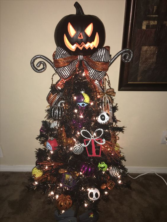 A Black Halloween Or Christmas Tree Decorated With Nightmare Before Christmas Ornaments, Lights, A Bow And A Giant Pumpkin