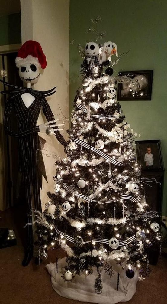 A Black Christmas Tree With Black And White Ribbons, White Garlands, Lights And Black And White Skellington Ornaments Plus Jack Skellington Next To It
