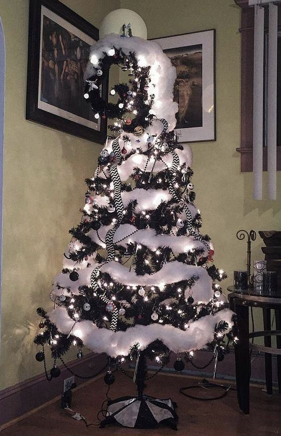 A Black Christmas Tree With Black And White Ornaments, White Cotton Snow, A Swirled Top And Striped Ribbons
