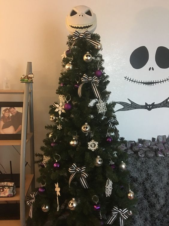 A Christmas Tree With Purple And Gold Ornaments And Bows Plus Jack Skellington Decorations For More Chic