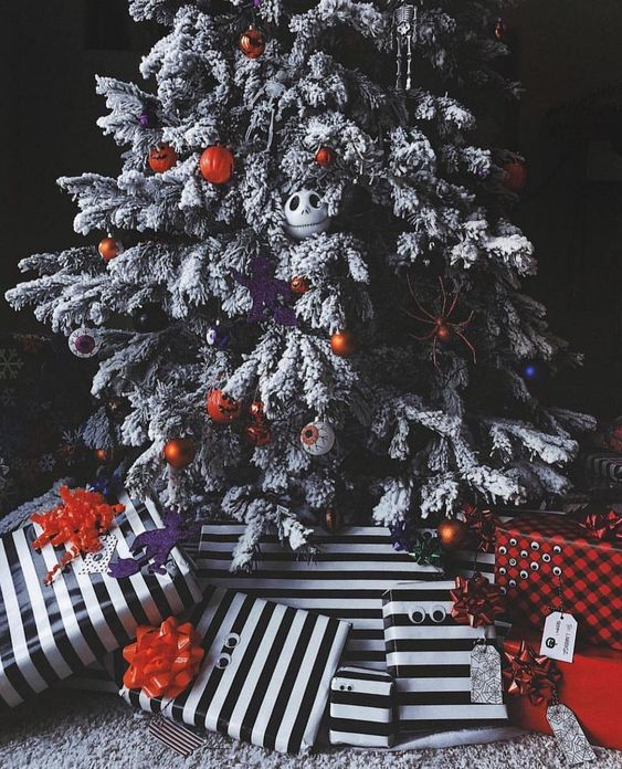 A Gorgeous Flocked Christmas Tree With Eyeball, Pumpkin And Jack Skellington Ornaments And Lights Plus Striped Gifts Under It