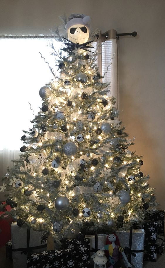 A Lit Up Silver Christmas Tree With Silver, Black And White Ornaments, Bells And A Jack Skellington Head On Top
