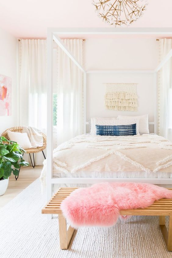 a bright feminine bedroom with a cnaopy bed, a wooden bench and a woven chair, a statement plant and a floral chandelier