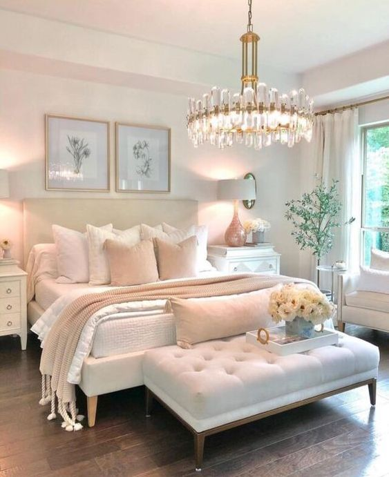 a glam and feminine bedroom with neutral furniture, a statement crystal chandelier, botanical artworks and real blooms