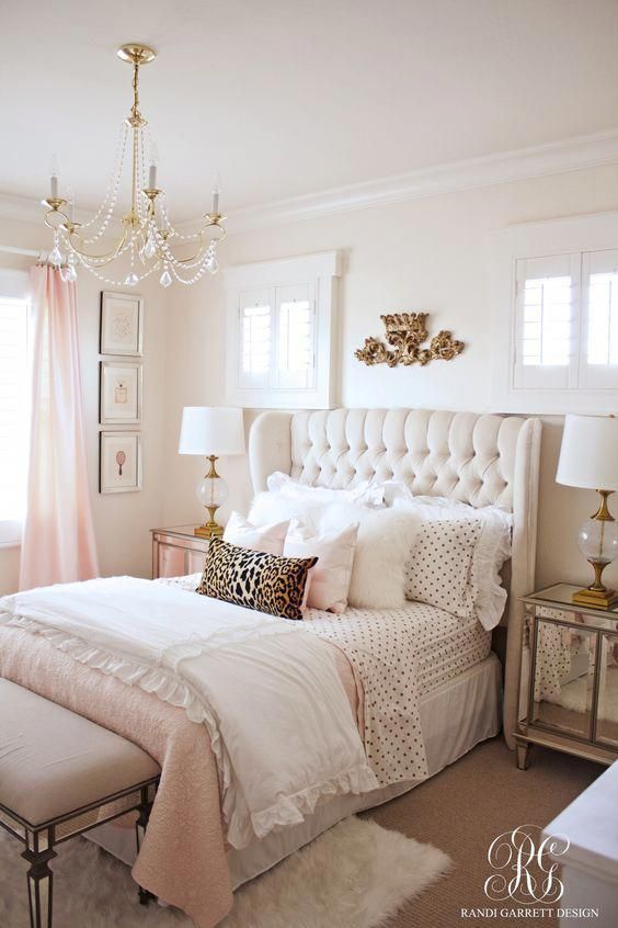 a glam girlish bedroom with an upholstered bed, mirrored nightstands and a bench, a crystal chandelier and touches of light pink