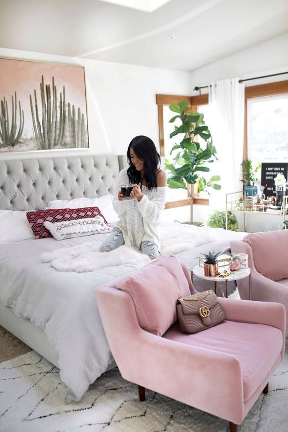 a fun feminine bedroom with a large grey bed, pink chairs, statement plants, a cactus artwork and boho pillows