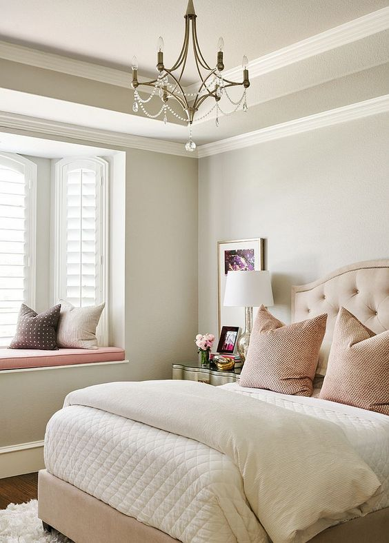 a neutral and pastel feminine bedroom with an upholstered bed, a crystal chandelier, blush and other pillows and a metallic nightstand