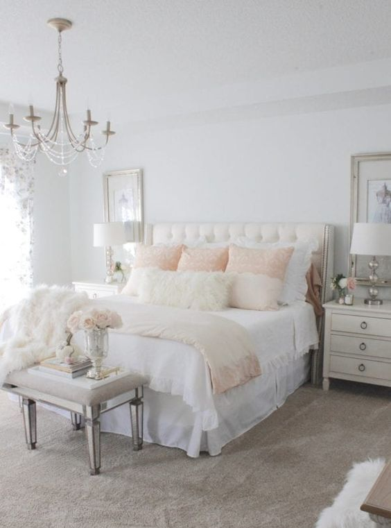 a neutral vintage bedroom with elegant furniture, neutral and pastel textiles, a crystal chandelier and large artworks plus mirror touches