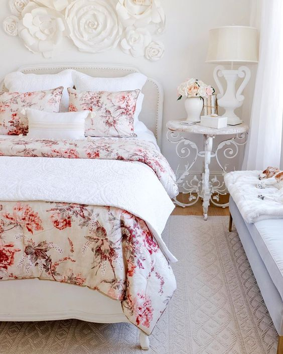 a refined Parisian style bedroom with chic furniture, floral bedding and a floral applique on the wall plus some blooms