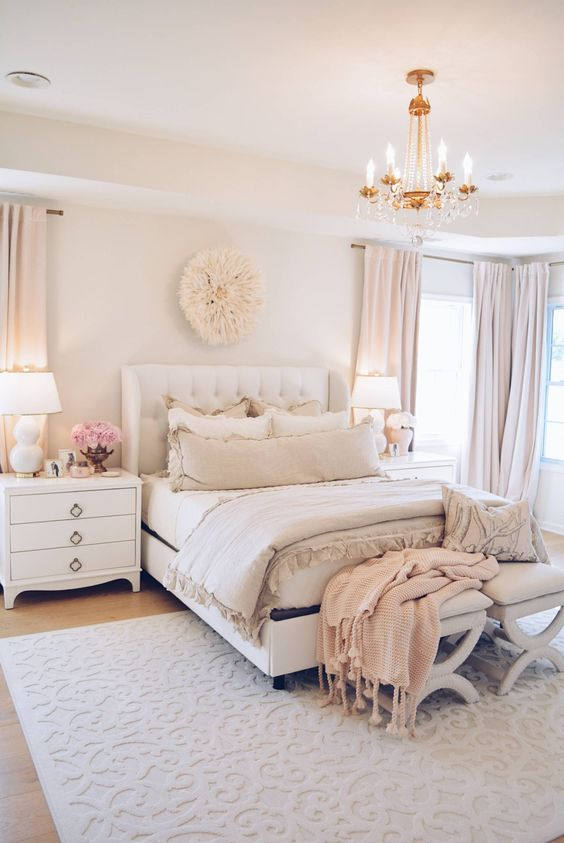 a welcoming feminine bedroom in neutrals and blush, with an upholstered bed, neutral furniture, a crystal chandelier and touches of blush