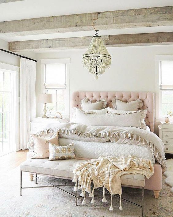 a relaxed feminine bedroom with wooden beams, a pink upholstered bed, a leather bench, neutral bedding and a chic chandelier