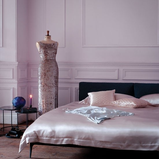 a refined modern bedroom with blush paneled walls, a black bed with blush silk bedding and a mannequin with a refined blush sequin dress