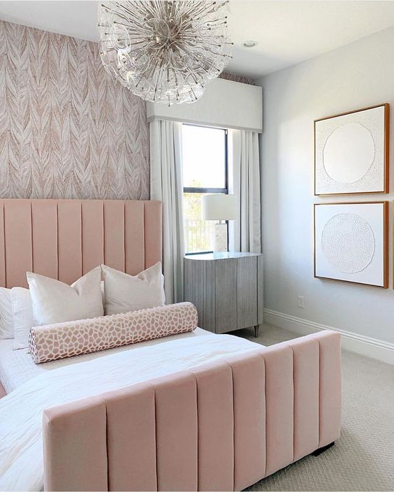 an elegant and laconic feminine bedroom with a wallpaper wall, a pink bed, a catchy chandelier and abstract artworks