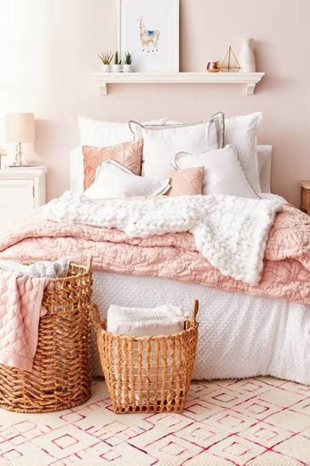 a relaxed feminine bedroom with blush walls, simple furniture, white and pink bedding, a shelf with art and a couple of baskets