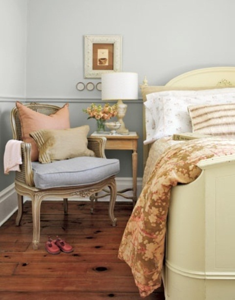 a welcoming powder blue bedroom with elegant vintage furniture, printed and solid bedding and a table lamp is chic and stylish